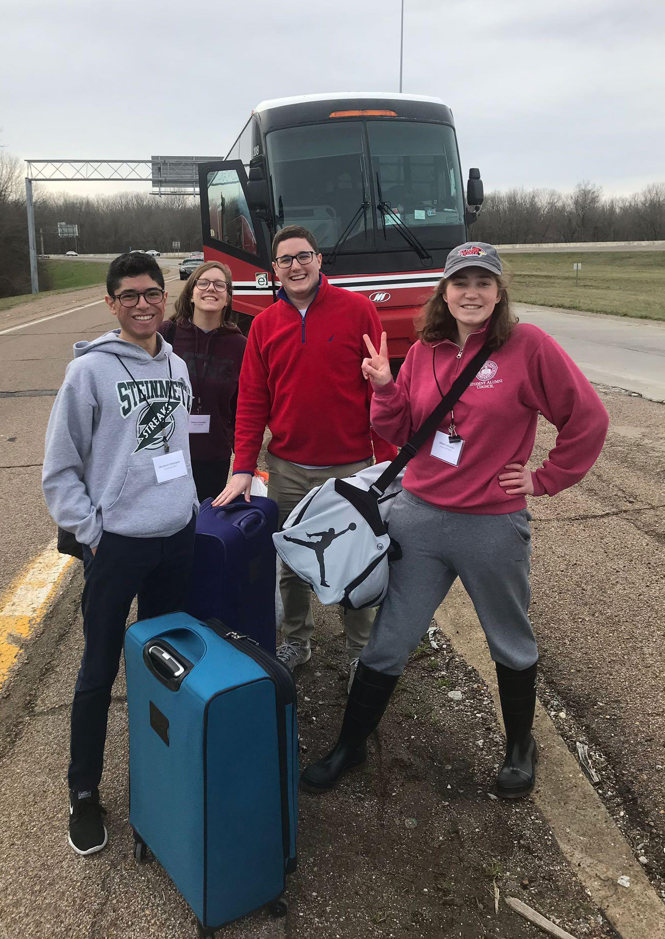 Students in front of a charter bus